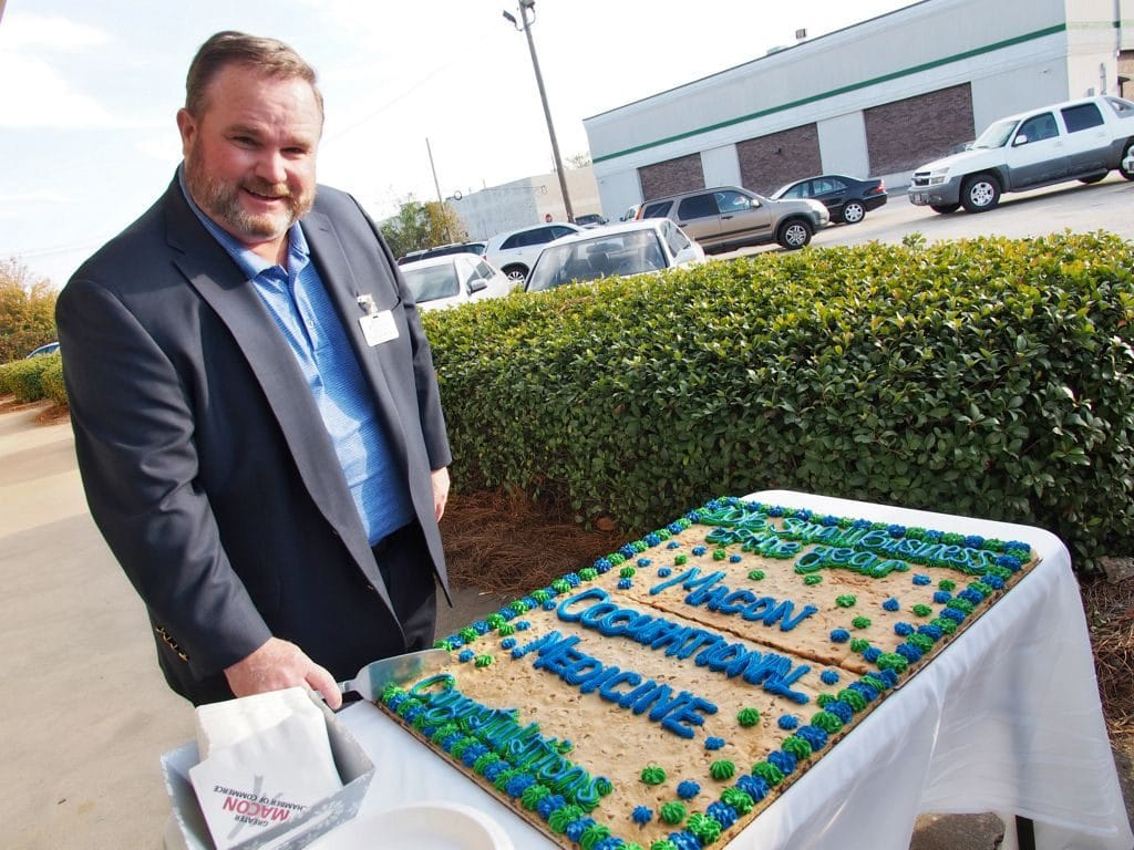 Leonard Beville cutting celebration cookie for the 2016 Small Business Industry Award